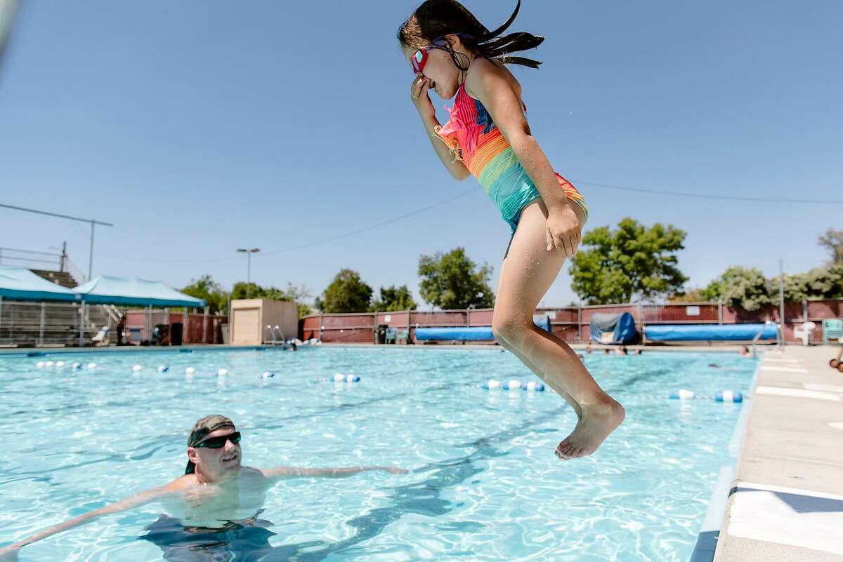 Mark Massey of Livermore watches as his daughter Sierra Massey jump in to the pool at the May Nissen Swim Center in Livermore, Calif, on Wednesday, August 14, 2019. A high pressure area over the Bay area will trigger dangerous levels of summer heat and heat advisories have been issued for portions of Alameda, Contra Costa and other central valley counties.