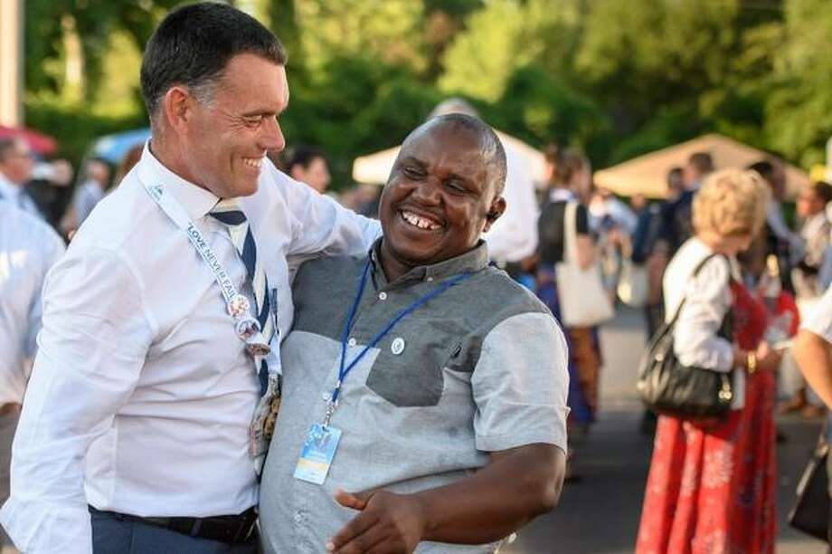 Wilfred Kimani, 47, of St. Louis greets a delegate visiting from England Photo: For The Intelligencer