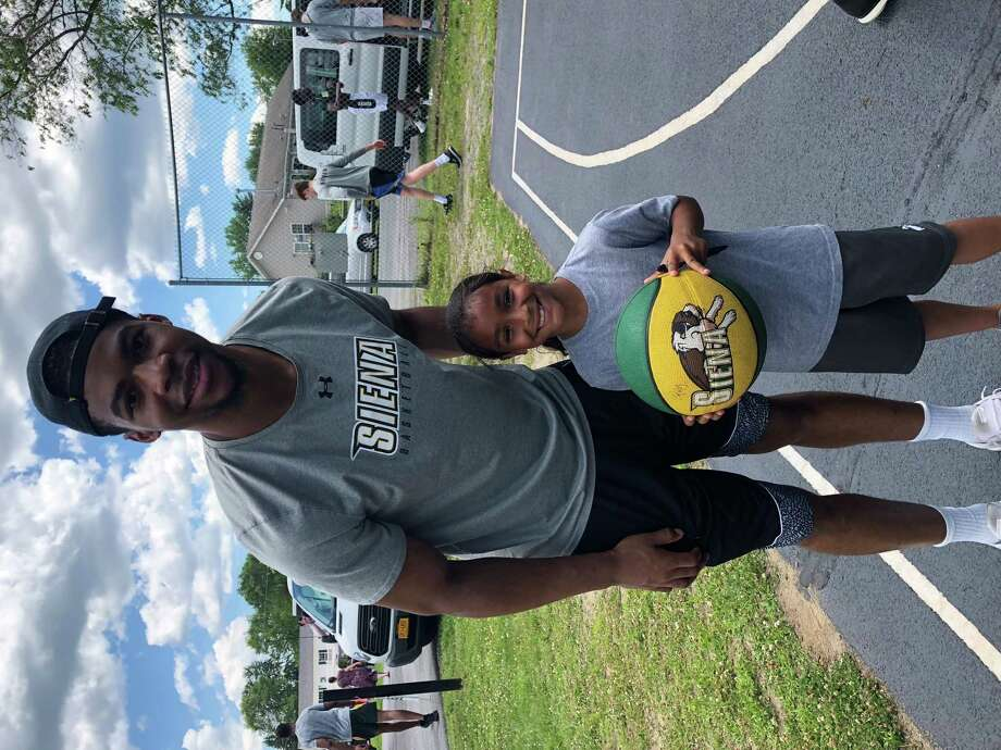 Siena basketball player Elijah Burns with Iyedan Ilert, age 7, who lives near the CAPTAIN Outreach Center and attends programs. Burns said he likes working at area camps to be a positive influence. (Courtesy Mike Demos of Siena Athletics)