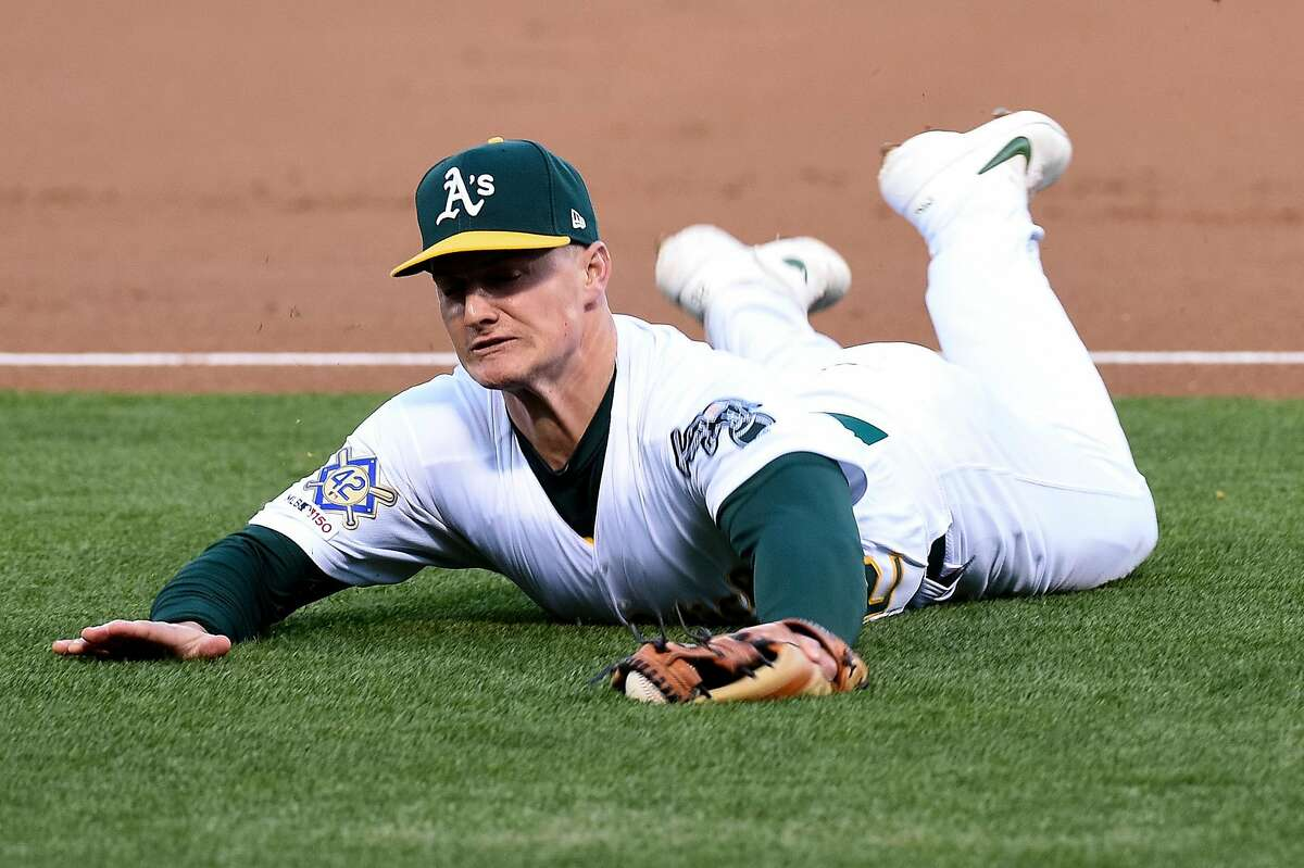 OAKLAND, CA - APRIL 16: Oakland Athletics third baseman Matt Chapman makes a diving catch in foul territory during the top of the first inning during the Major League Baseball game between the Houston Astros and the Oakland Athletics at Oakland-Alameda County Coliseum on April 16, 2019 in Oakland, CA.(Photo by Cody Glenn/Icon Sportswire via Getty Images)