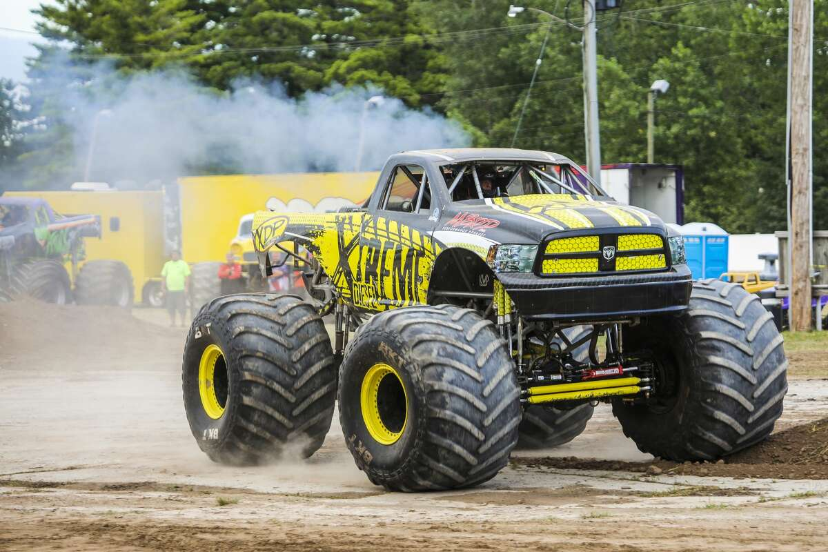 Monster truck drivers race around a track on Wednesday, Aug. 14, 2019 at the Midland County Fair. (Katy Kildee/kkildee@mdn.net)