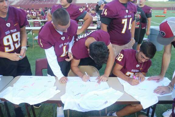 Members of last year's football team autograph T-shirts during the inaugural Football Festival. Flynn said the Festival shows the players how much the city supports the team and high school athletics in general.