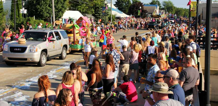 The Parade of Tropical Fools winds its way through a packed crowd in Caseville. Jimmy & the Parrots had a concert shortly after the parade finished. Photo: Andrew Mullin/Huron Daily Tribune