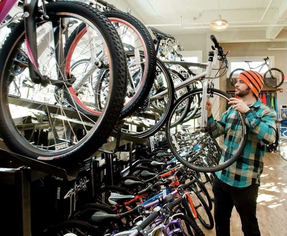 Ridgefield Bicycle Company mechanic Adam Ray pulls a bike off the rack at the store on Danbury Road in Ridgefield. Wednesday, Nov. 20, 2013 Photo: Scott Mullin / Scott Mullin / The News-Times Freelance