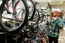 Ridgefield Bicycle Company mechanic Adam Ray pulls a bike off the rack at the store on Danbury Road in Ridgefield. Wednesday, Nov. 20, 2013