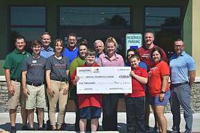 Two Special Olympics Illinois athletes Sammy Newberry (center left) and Cole Stone (center right) of Loving Life Agency recieve a $5,000 check from McAlister's Deli in Edwardsville, represented by Aggressive Developments of Missouri, LLC franchisee Matthew Fox and restaurant staff, alongside Special Olympics Illinois representatives Katy Gruen, Justin Dunning, and Steve Whitlatch.