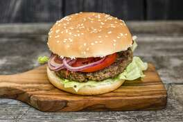 Homemade burger with lettuce, meat, tomato and onion on chopping board