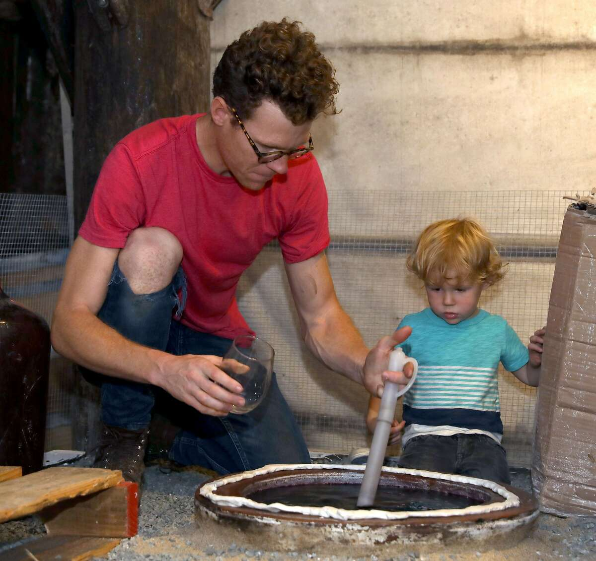 Winemaker Caleb Leisure (left) tastes wine from a qvevri, imported from the Republic of Georgia, with his two year old son Henry Leisure (right) at Coturri Winery on Tuesday, Aug. 13, 2019, in Glen Ellen, Calif.