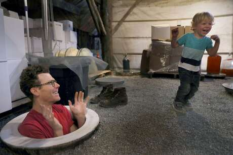 Winemaker Caleb Leisure plays with his two year old son Henry Leisure from inside an 85-liter qvevri, which is empty right now as he awaits new grapes from the 2019 harvest. Photo: Liz Hafalia / The Chronicle