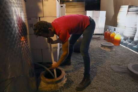 Winemaker Caleb Leisure cleans one of his qvevri, which is buried underground, in the model of traditional Georgian wines. Photo: Liz Hafalia / The Chronicle