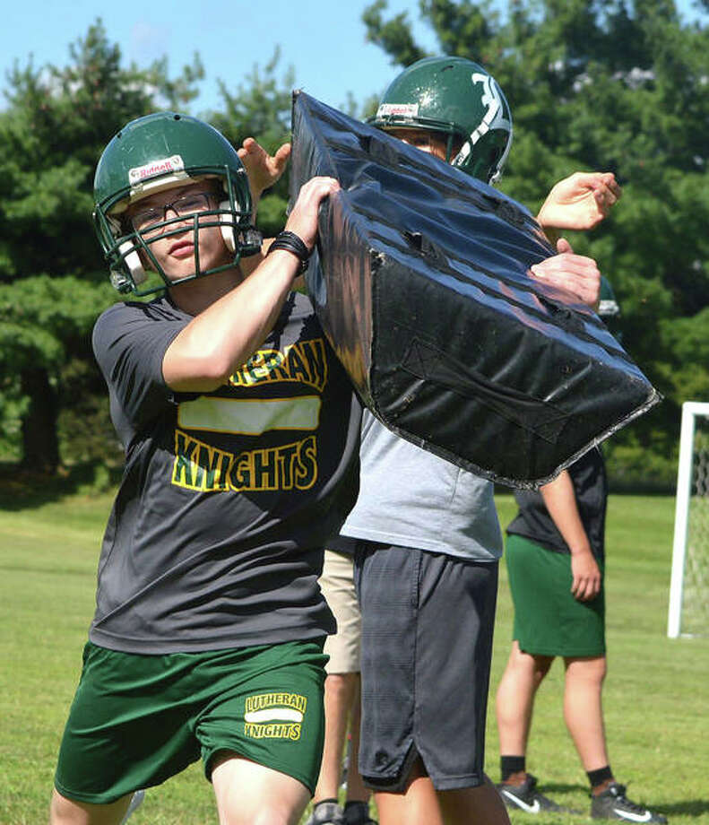 Metro-East Lutheran players perform blocking drills on Tuesday in their second day of practice. The Knights moved outdoors after extreme heat and a wet field forced them to play indoors on Monday. Photo: Scott Marion/The Intelligencer