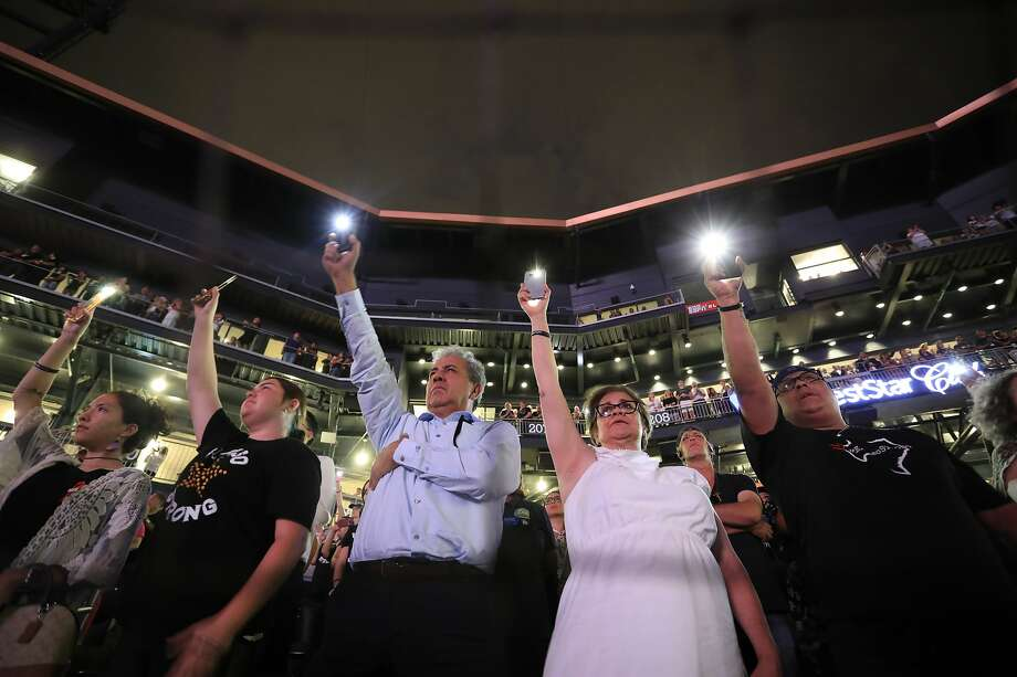 Memorial service attendees hold up cell phones as the names of the victims of the mass shooting are read in El Paso. Photo: Jorge Salgado / Associated Press