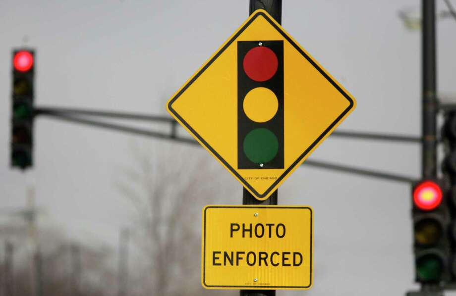 Texas Gov. Greg Abbott signed a law June 1, banning red-light traffic cameras in Texas. A reader says red-light cameras should be enforced along with a new city council. Photo: M. Spencer Green /Associated Press / Copyright 2019 The Associated Press. All rights reserved.