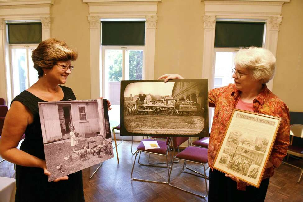 Karin Krasevac-Lenz, executive director of the Rensselaer County Historical Society, left, Stacy Pomeroy Draper, curator RCHS, right, hold photographs depicting the county's working past on Thursday, Aug. 15, 2019, Troy, N.Y. The Rensselaer County Historical Society is 1 of 10 small museums nationwide to be selected as part of a Museums on Main Street program to expand the Smithsonian's reach into local communities by providing a framework for an exhibition about how Americans work. (Will Waldron/Times Union)