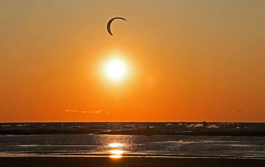 High winds on the Saginaw Bay recently created the perfect opportunity for wind surfing, as the sun set at the Caseville beach. Photo: Bill Diller/For The Tribune