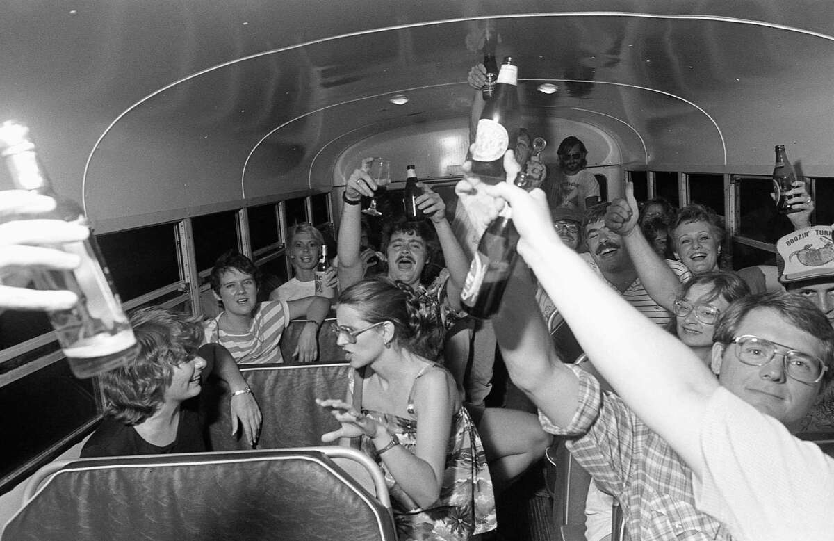 06/11/1983 - Revellers toast the start of the First Annual Foam Rangers Pub Crawl as the bus takes them to their next stop.