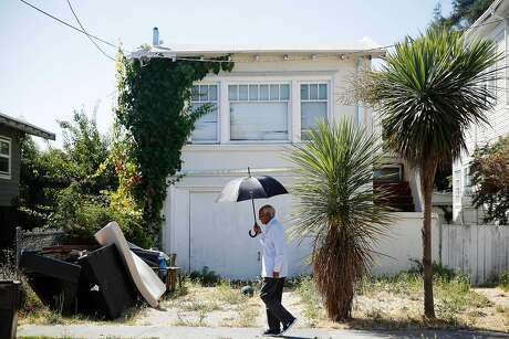 Berhane Woldeabzghi of Oakland, takes cover from the sun under the shade of an umbrella as he walks on 59th Street during a walk around his neighborhood on Thursday, August 15, 2019  in Oakland, Calif.