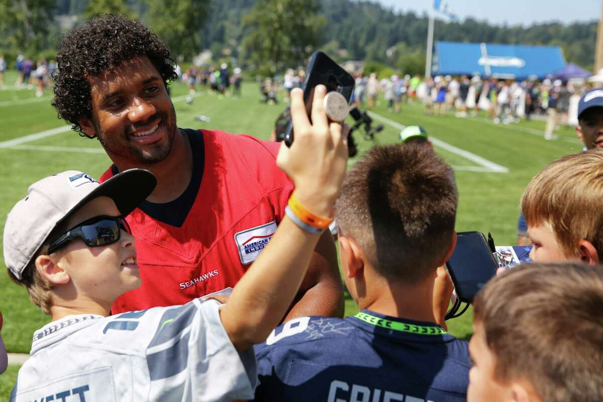 Kids take selfies with Russell Wilson after the Seahawks training camp, Thursday, Aug. 15, 2019.