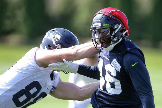Tight end Will Dissley (88) and line backer Jawuan Johnson (46) run a play during the Seahawks training camp, Thursday, Aug. 15, 2019.