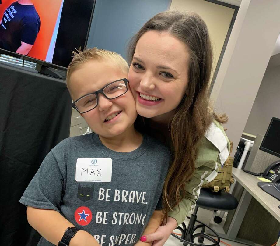 Max Boatwright, 8, pauses for a sweet embrace from his Mackenzie Sadler, his bone marrow donor, at the grand opening for an expansion of Cellular Life Solutions at the Gulf Coast Regional Blood Center on Wednesday, Aug.14. Photo: Courtesy By Gulf Coast Regional Blood Center