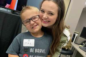Max Boatwright, 8, pauses for a sweet embrace from his Mackenzie Sadler, his bone marrow donor, at the grand opening for an expansion of Cellular Life Solutions at the Gulf Coast Regional Blood Center on Wednesday, Aug.14.