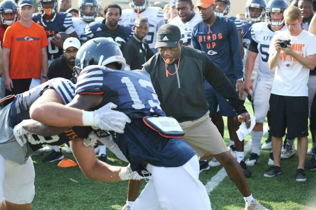 """UTSA football coach Frank Wilson, watching two players engage in a """"bird cage"""" drill during a recent practice, established a leadership council that will report to Wilson and his staff to have a voice in the program's direction."""