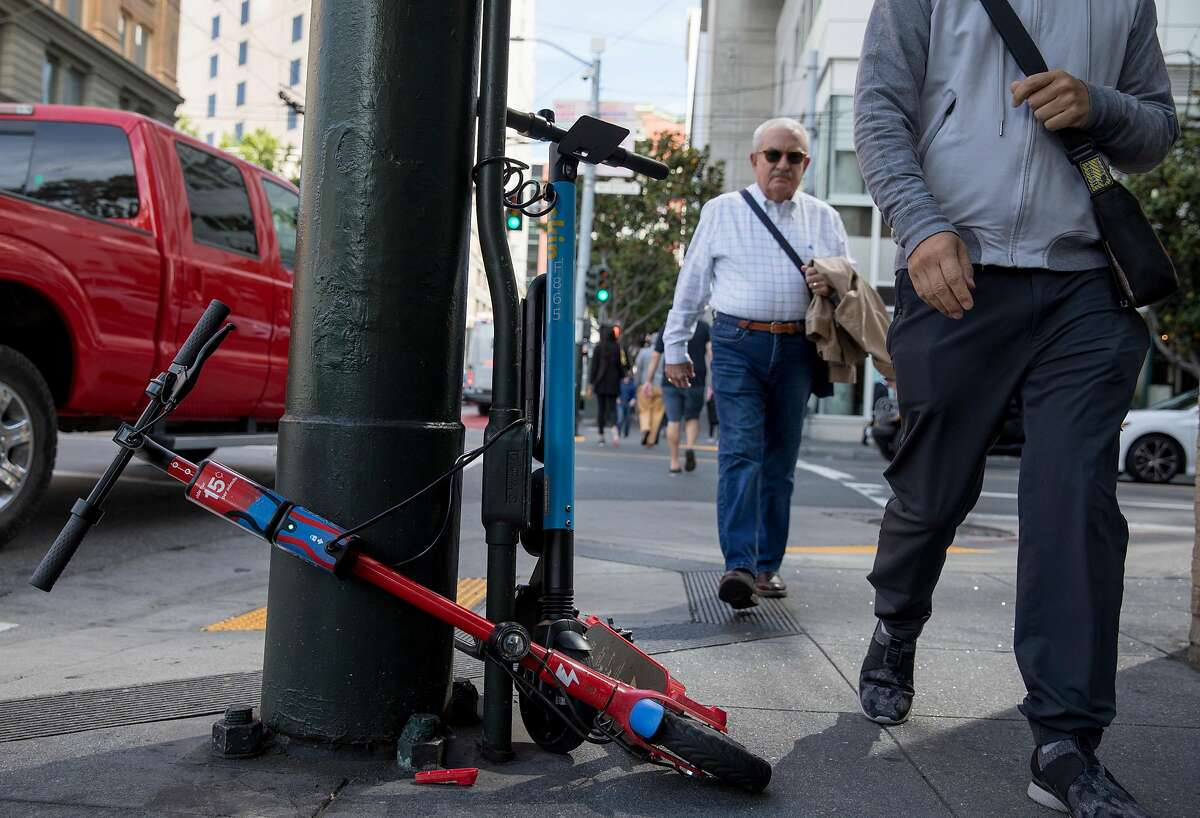 Two men pass a duo of Skip and Scoot scooters on the corner of New Montgomery and Mission streets in the South of Market district of San Francisco, Calif. Friday, June 28, 2019.