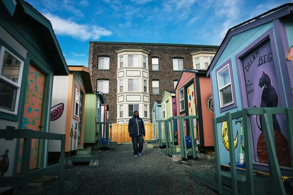 Kenyatta Webb walks through the True Hope Village on East Yesler Way where he has lived with his 14-year-old son, Milchia, for the past two months, Oct. 28, 2018. (Genna Martin, seattlepi.com)