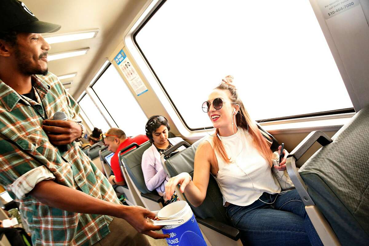 Tone Oliver (l to r) accepts a donation fromBrittany Pilgram of Oakland after performing on a BART train on Wednesday, August 14, 2019 in Oakland, Calif.