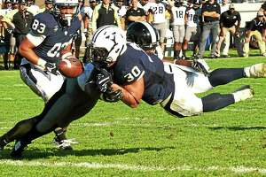 Yale running back Tyler Varga, right, scores a touchdown against Army cornerback Chris Carnegie and then loses the ball after crossing the goal line during the fourth quarter on Sept. 27. 2014.