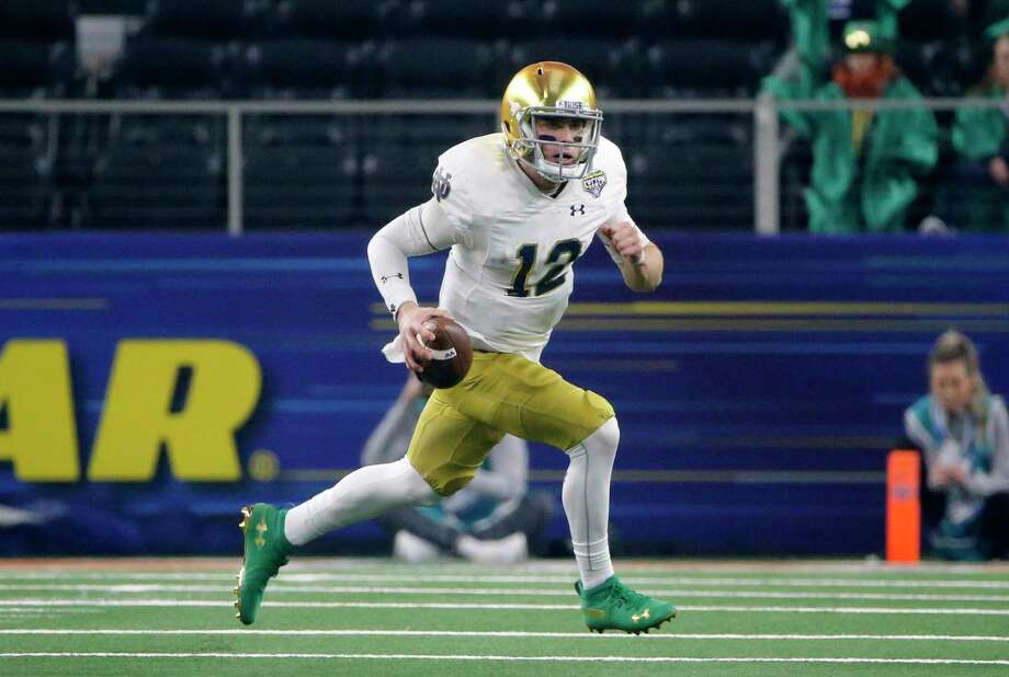 FILE - In this Dec. 29, 2018, file photo, Notre Dame quarterback Ian Book (12) runs the ball against Clemson during the NCAA Cotton Bowl semifinal playoff football game, in Arlington, Texas. Upon his return to campus last winter, Book immediately worked on his leadership skills and also making the difficult and tight downfield passes. Book was rewarded when he was named one of the teama€™s seven captains. (AP Photo/Michael Ainsworth, File) Photo: Michael Ainsworth / Copyright 2018 The Associated Press. All rights reserved.