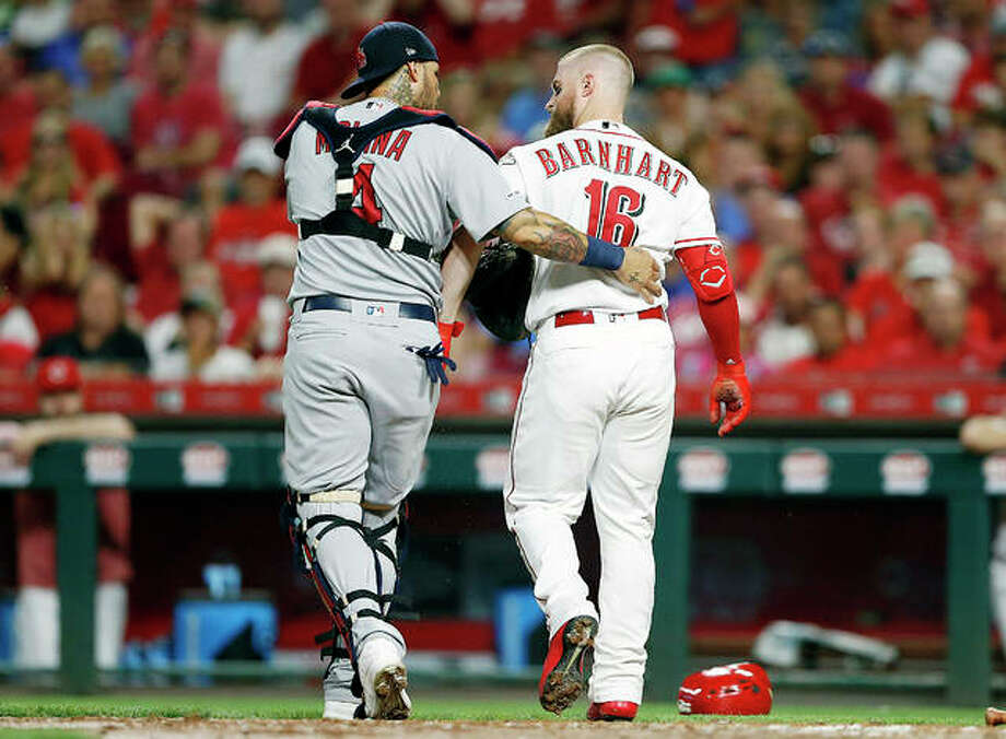 Cardinals catcher Yadier Molina (4) checks on the condition of Cincinnati Reds' Tucker Barnhart (16) after Barnhart was hit on the head by a pitch thrown by the Cardinals' Michael Wacha iin the fifth inning of Thursday night's game in Cincinnati. Photo: AP Photo