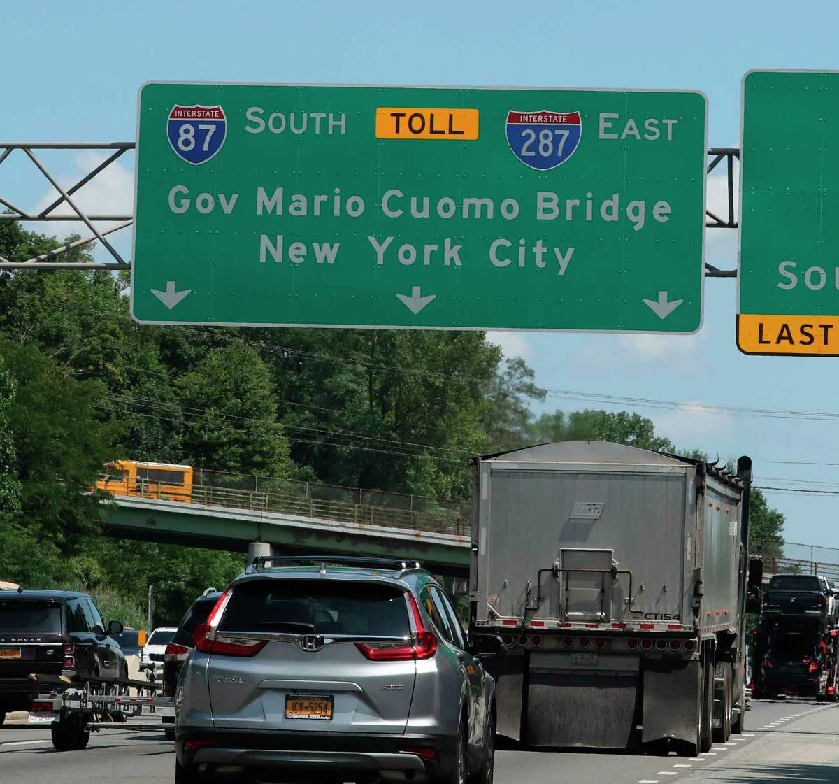 In this Aug. 1, 2019, photo, traffic passes under a sign for the Gov. Mario M. Cuomo Bridge on the New York State Thruway in Nyack, N.Y. The New York State Department of Transportation said Thursday, Aug. 15, 2019 that roughly year-old signs for the suburban bridge named after the former governor are being patched over because his middle initial is missing. (Peter Carr/The Journal News via AP)