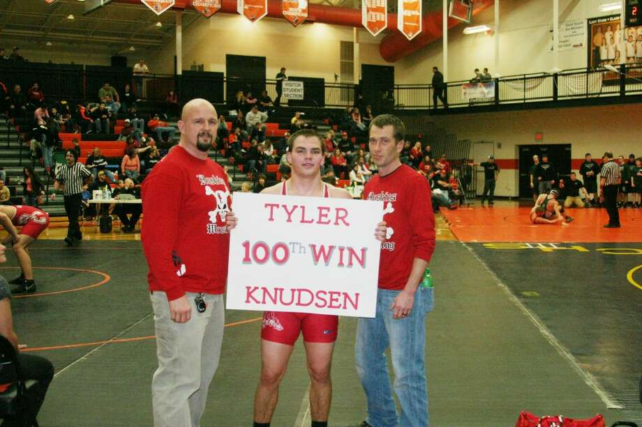 Tyler Wins: Senior Tyler Knudsen celebrates with his coaches after earning his 100th career victory on January 12. (Photo/Bryan Warrick)