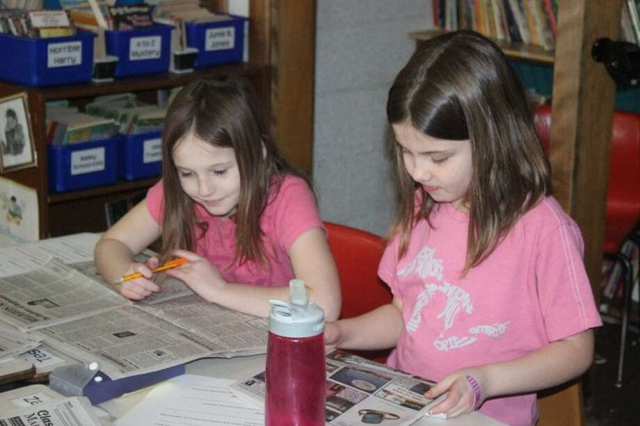 LOOKING FOR EXAMPLES: Platte River Elementary students study the Record Patriot for the NIE lesson. The students are learning what goes into making a newspaper.