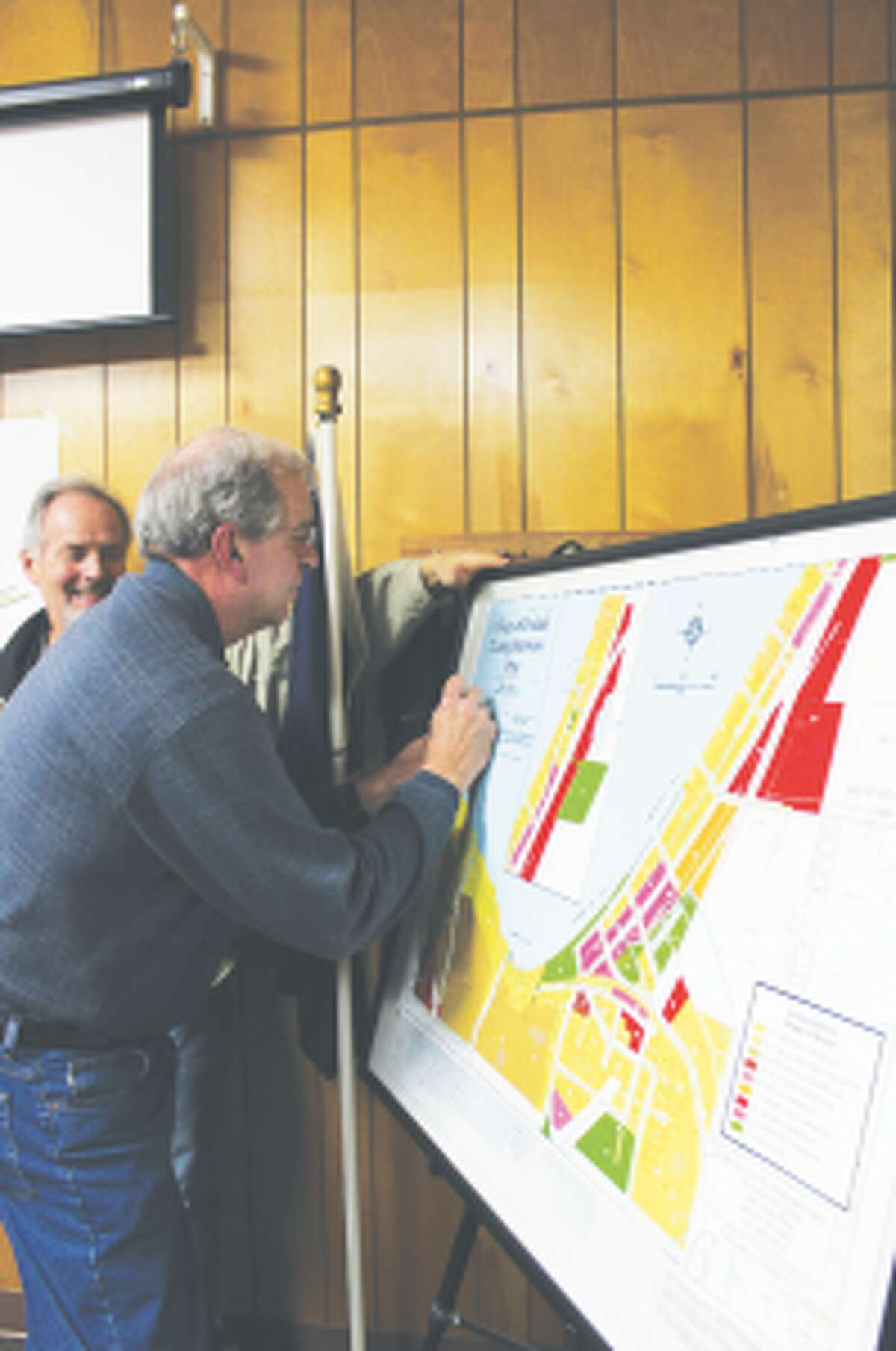 New Zoning: Ronald Edwards, zoning administrator for the Village of Beulah, watches as Councilman Don Hook signs the new zoning map, which was approved by the council after several public hearings held on the changes. Most of the changes involved errors in the original map, but 3 parcels zoned rural conservation were changed to residential 1 in order to match the parcels around them.