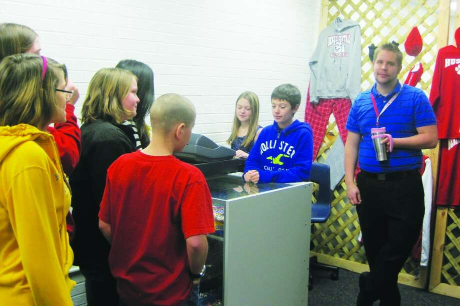 BCMS store open: Benzie Middle School 8th grader Brianna Smith and 7th grader Ryan Sass, along with Benzie Sunrise Rotarian David Sylvester, sell school logo items and snacks to students at the Benzie Middle School Store. (Photo/Kris Thomas)