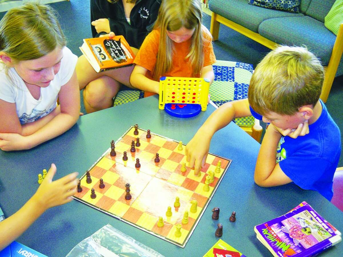 Child's Play: Augie Pasche plays chess with his friends at a summer game program at the Benzie Shores District Library. The library hold similar children's activity hours every Tuesday of the week, giving younger children and their parents something to do during the cold winter months. (Courtesy Photo)