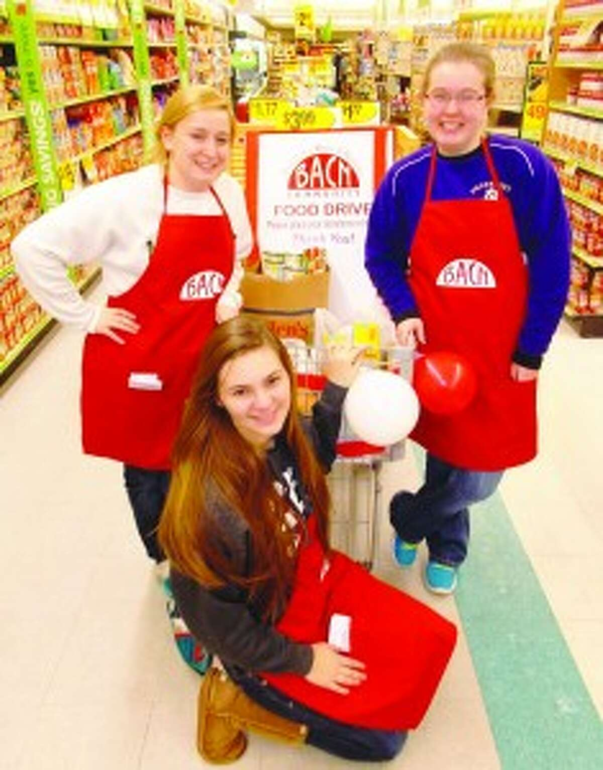 Helping Neighbors: Frankfort-Elberta High School National Honor Society Seniors Autumn Catterall, Sierra Willsey and Marissa Fisher urge shoppers to donate food items for BACN's Chase the Chill winter food drive at Glen's Food Market. Area residents were able to contribute to the drive at locations throughout the county, and for the first time, summer residents were able to donate online. (Courtesy Photo)