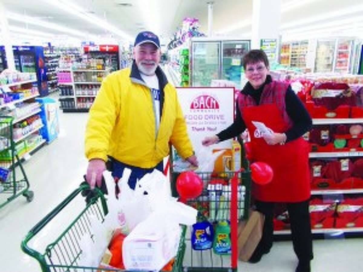"""BACN Donation: Bill Witowski fills the BACN donation cart at Shop and Save in Benzonia manned by Lynn Bekkering from Blaine Christian Church. people could donate money to the cause at the register through the """"scan a buck"""" program as well. (Courtesy Photo)"""
