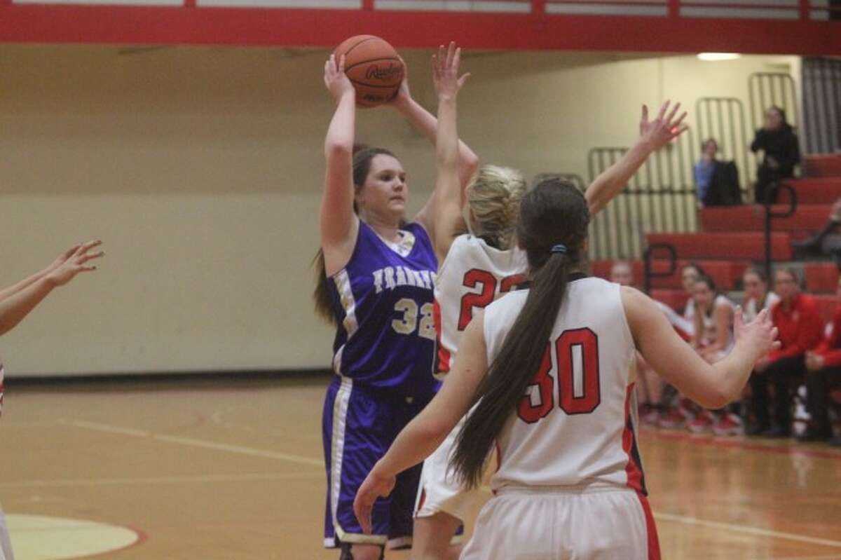 BATTLE IN SUTTONS BAY: Frankfort senior Brianna Miller (32) tries to get past the tough Suttons Bay defense during the Feb. 5 game. The Panthers won the nail-biter meeting. (Photos/Bryan Warrick)