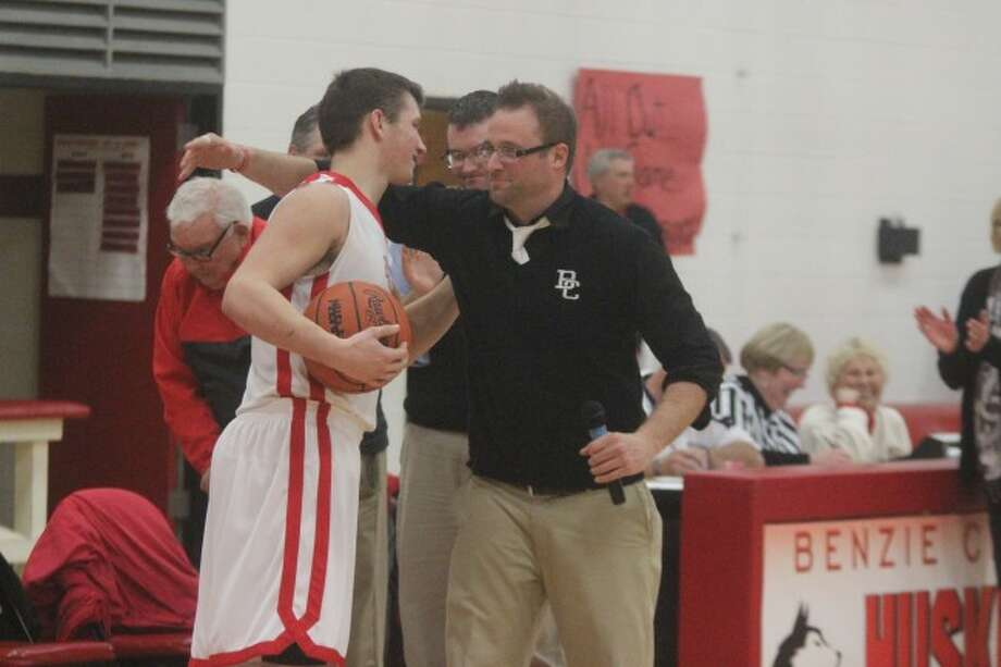 BIG BLOCKER: Benzie Central head coach Matt Olson gives senior Aaron Whaley the game ball after the Huskies win against Manistee. During the contest, Whaley broke the school record for most career blocked shots. (Photos/Bryan Warrick)