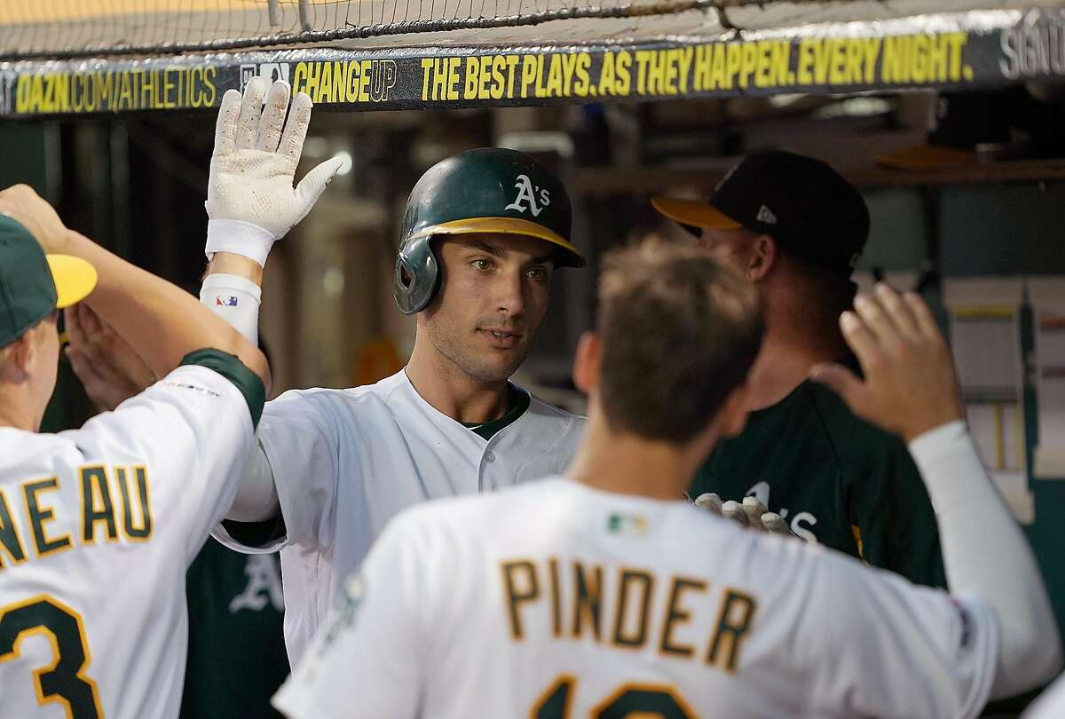 OAKLAND, CA - AUGUST 15: Matt Olson #28 of the Oakland Athletics is congratulated by teammates after hitting a three-run home run against the Houston Astros in the bottom of the fourth inning at Ring Central Coliseum on August 15, 2019 in Oakland, California. (Photo by Thearon W. Henderson/Getty Images)
