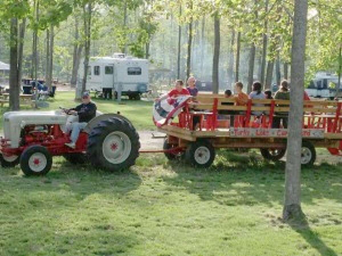 HAY RIDE: Kids and parents ride the hay wagon at the Turtle Lake campground. The ride is pulled by a restored 1958 Ford tractor and gives tours of the lake, beaches and woods. (Courtesy photo)