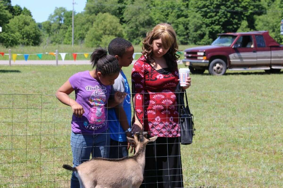 BUSY WEEKEND: Christina Stevens and her children, Corvonta Chandler and Christian Atkinson check out the animals at the Blazing Fires of Revival big-tent event at Hilltop Tabernacle Saturday. (Photo/Colin Merry)
