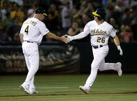 Oakland Athletics' Matt Chapman, right, is congratulated by third base coach Matt Williams (4) after hitting the go-ahead home run in the eighth inning of the team's baseball game against the Houston Astros on Thursday, Aug. 15, 2019, in Oakland, Calif. (AP Photo/Ben Margot)