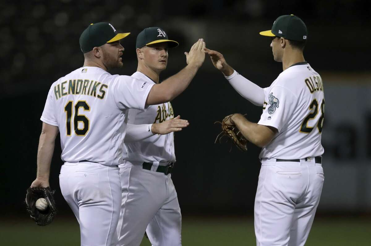 Oakland Athletics' Liam Hendriks, left, celebrates the A's 7-6 win over the Houston Astros with Matt Chapman, center, and Matt Olson after the baseball game Thursday, Aug. 15, 2019, in Oakland, Calif. (AP Photo/Ben Margot)