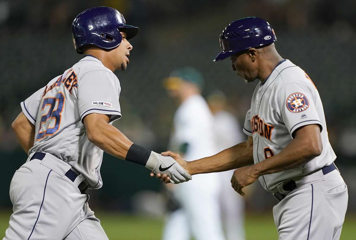 OAKLAND, CA - AUGUST 15: Michael Brantley #23 of the Houston Astros is congratulated by third base coach Gary Pettis #8 after his solo home run against the Oakland Athletics in the top of the fifth inning at Ring Central Coliseum on August 15, 2019 in Oakland, California. (Photo by Thearon W. Henderson/Getty Images)