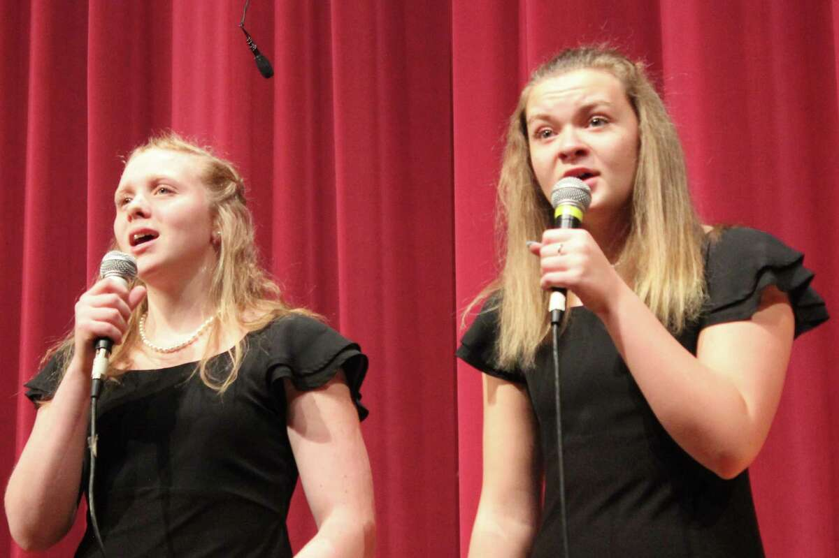 """Maci Kunkel (left) and Melia Lorenz (right) sing """"Snow Begins to Fall"""" as a duet. (Photo/Robert Myers)"""