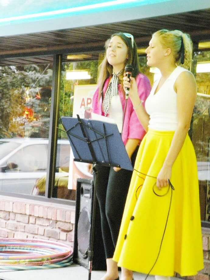 CONEY SISTERS: (ABOVE) Chelsea Fries (left) and Amanda Troyer sing songs from the 1950s at a past Cruise Night at A&W in Frankfort. Music from the era is a big part of the event. This year's festivities are set for Friday.